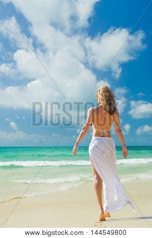 Woman in white  walking on the beach in the summertime