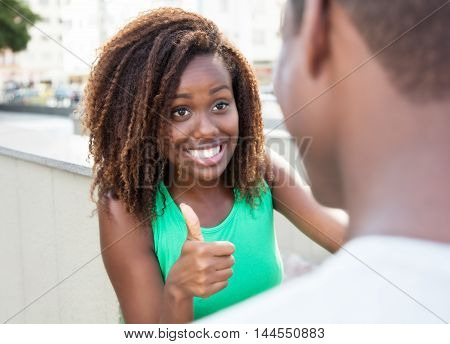 Laughing african girl showing thumb to boyfriend in the summer in the city