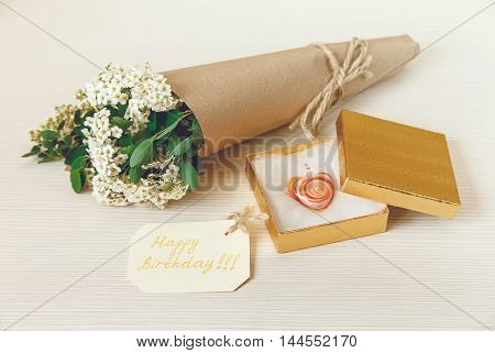 Yellow Birthday Card with Golden Present Box with Glass Heart. Bouquet White Small Flowers in Brown Craft Paper with String