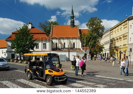 Krakow Poland - August 25 2016: St. Giles street. On the left there is the Church of St. Giles on the right historic townhouses standing along the street. On the street is electric vehicle to carry tourists.