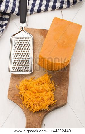 irish mature grated cheddar cheese with grater on a wooden board
