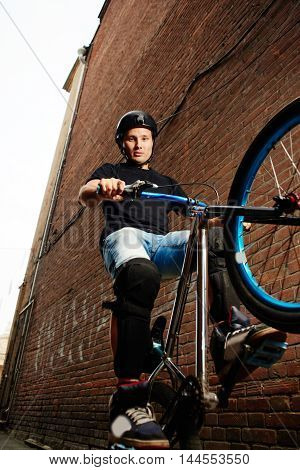 The guy is a cyclist riding on the rear wheel of the bike near the wall of the red brick building