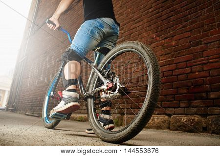 The guy was a cyclist on the bike near the wall of the red brick building