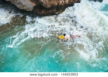 Outdoors aerial view of surfer swimming on a board near huge blue ocean wave and dangerous cliff in Bali, Indonesia