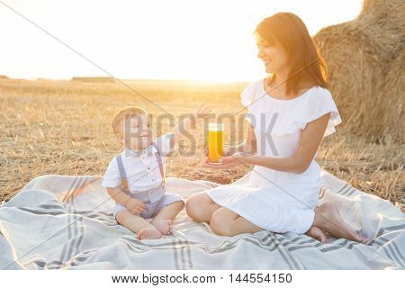 Small cute baby with his mother on a picnic. Mom offers juice to your child. Happy family healthy food.