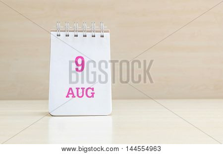 Closeup surface note book with pink 9 aug word in page on blurred brown wood desk and wood wall textured background with copy space under window light