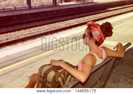 Young sexy woman backpacker sitting on bench on railway station. Travel concept.