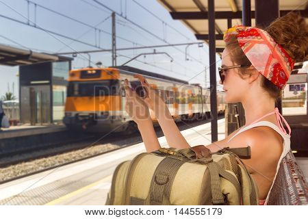 Young sexy woman backpacker sitting on bench on railway station and charting on smart phone. Travel concept.