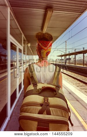 Young sexy woman backpacker waiting for train on platform on railway station. Travel concept. Travel concept.