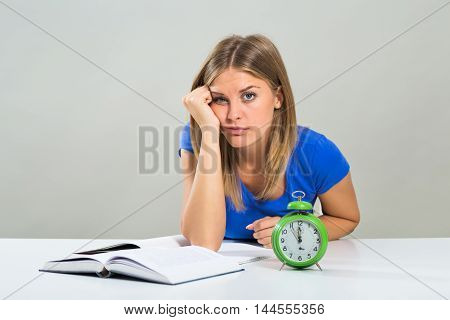 Sad female student doesn't want to study,but the clock is showing that there is not to much time.