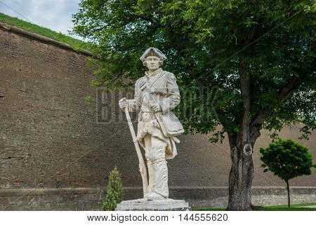 Soldier statue against Walls of Eugen of Savoia Bastion in Citadel of Alba Iulia city in Romania