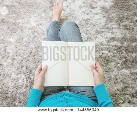 Closeup asian woman sitting on gray carpet at floor in the house textured background for read a book in relax time free time at house concept