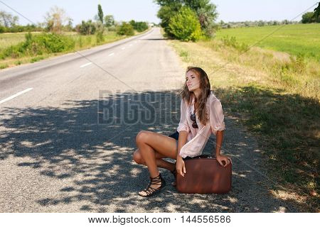 Tired woman in the summer with a suitcase hitchhiking on the road in the countryside