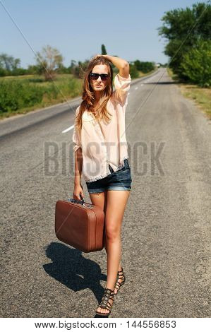 Young woman in the summer with a suitcase hitchhiking on the road in the countryside