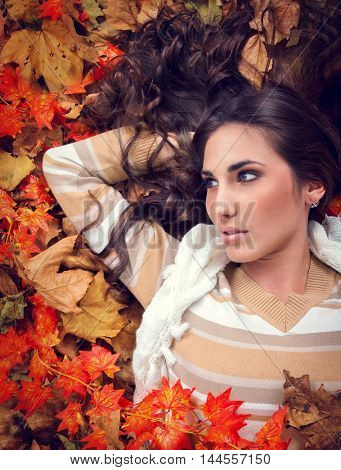 young woman in autumn orange leaves, outdoor