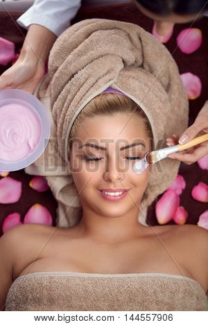 facial mask treatment of charming woman in spa salon