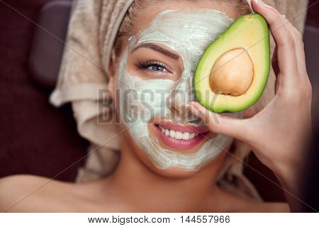 portrait of a young woman applying natural avocado mask on her face