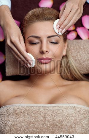 Young pretty woman on professional face treatment from beauty therapist