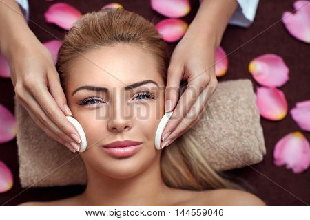 Peaceful brunette getting facial treatment from beauty therapist in the health spa