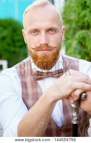 Portrait of stylish blonde man with red beard