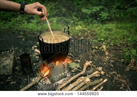 Man cooking on fire in forest