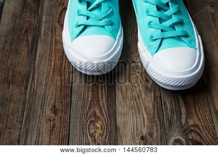 Blue sneakers on empty Brown parquet