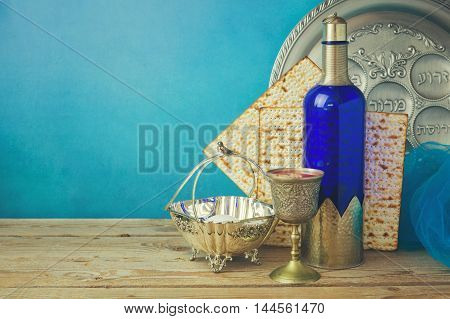 Passover background with matzo and wine on wooden vintage table. Seder plate with hebrew text says bone lettuce apple and nuts.
