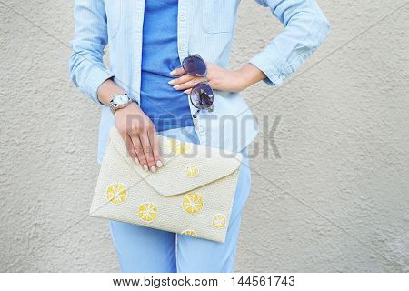 Young woman with fashion details on concrete wall background