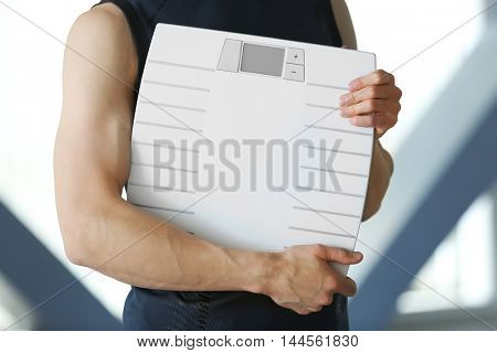 Man holding weight scale, close up
