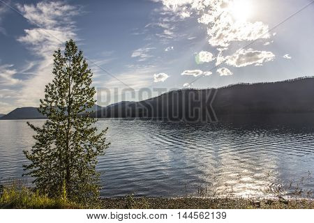 View of Lake McDonald with reflection of the sun and sun rays through clouds along Going-to-the-sun road in Glacier National Park Montana United States.