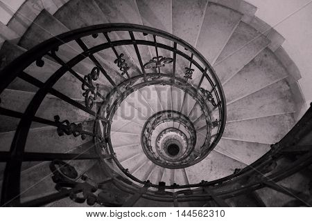 black - white photo of a spiral staircase in an old house