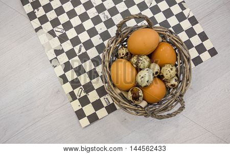 Plate with quail eggs and chicken eggs. Quail eggs in a wooden bowl. place for text. nutrition protein diet. Top view flat lay with copyspace slogan or text message. colorful background