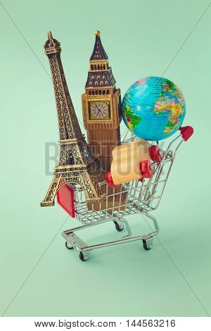 Travel around the world concept. Shopping cart with souvenir from around the world. Retro filter effect