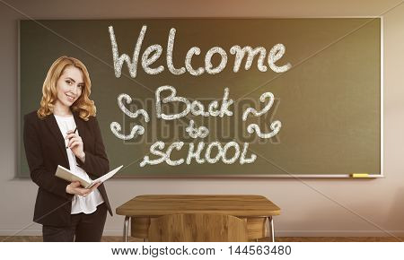 Smiling teacher with red hair holding notepad and standing near blackboard with Welcome back to school text. Concept of new school year. Toned image