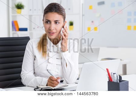 Businesswoman Talking On Cellphone In Office