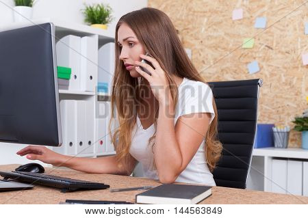 Serious secretary is checking her boss's schedule while talking with his business partner on phone. Concept of good assistant
