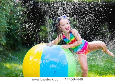 Funny laughing little girl in a colorful swimming suit playing with toy ball garden sprinkler with water splashes having fun in the backyard on a sunny hot summer vacation day