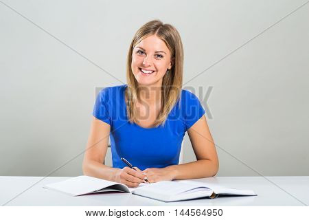Portrait of beautiful female student sitting at the table and studying.