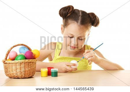 Cute girl painting Easter eggs on white background