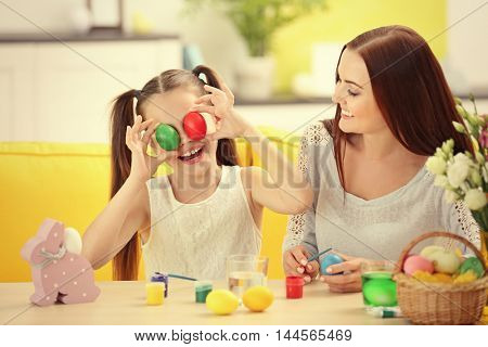 Mother and daughter with Easter eggs having fun at home