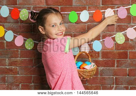 Cute girl with Easter eggs on vivid background