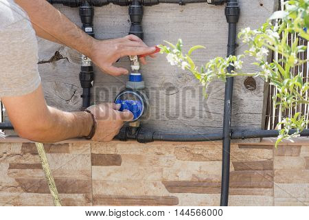 a person is setting the clock irrigation, a person gardening watering with a automatic irrigation system,