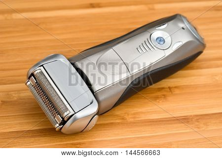 Electric shaver on a wooden table, close-up .