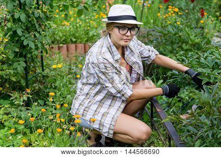 Young beautiful woman gardener working in her garden. Model looking in camera