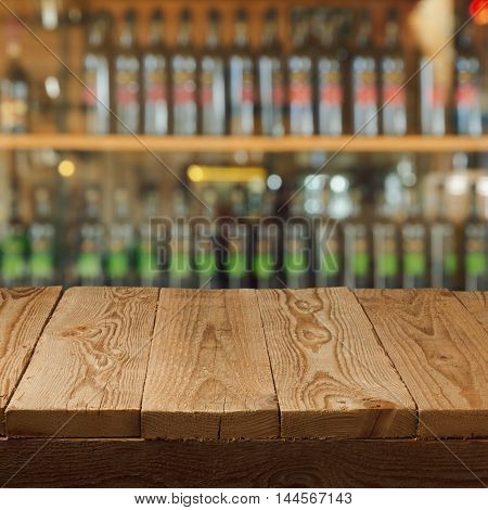 Empty wooden table over wine store background