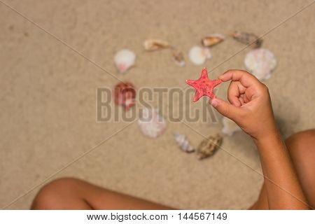Child holds starfish. Child hand with starfish. Sea shells on sandy beach. Summer background. Top view
