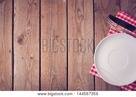 Wooden background with plate and silverware. View from above