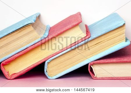 Stack of colorful books grungy blue background free copy space. Education essential for self improvement gaining knowledge and success in our careers business and personal lives.