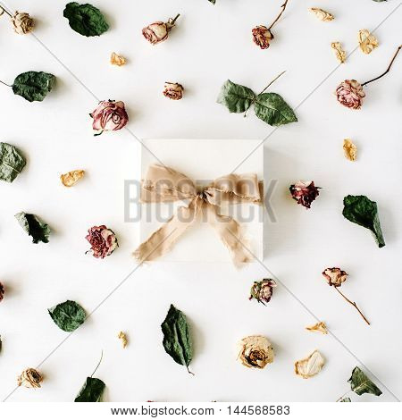 white gift box with brown ribbon and bow on white decorated with roses and dry leaves background. flat lat top view