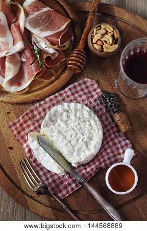 Camembert cheese cold cuts and glass of red wine